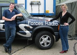 Neil Carter and Hermina Graham pose next to the BFBS Land Rover...